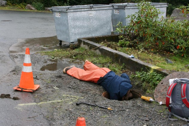 ADEC responder, Crystal Smith, checks manhole for potential pathways.