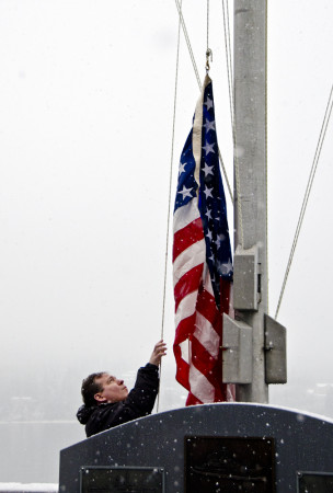 Col Duff Mitchell, retired from Army National Guard, raises the American flag.