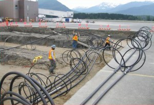 Workers install piping at the Juneau International Airport project [36]