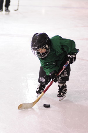 Morgan Sowa swipes at the puck during during JDIA's Learn to Play event Saturday at Treadwell Ice Arena.