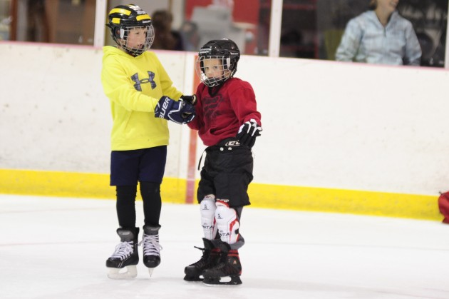 Gabe Miller assists Caleb Friend on the ice during JDIA's Learn to Play event Saturday at Treadwell Ice Arena. Miller was among many advanced players willing to work with kids skating for the first time.