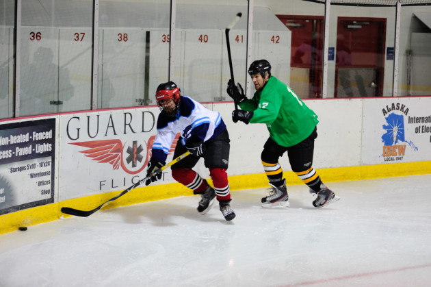 The Green team's Mason Morriss chases Jason Bluhm around the boards behind the Green team's net.