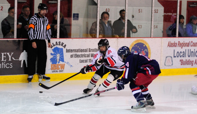 Juneau's Kaipo Tseu looks for an open teammate for a pass while trying to evade North Pole defenseman Daniel Volsky during the two-game series at Treadwell Ice Arena.