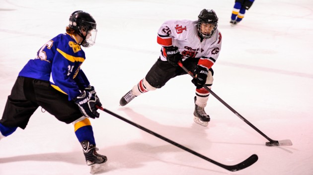 Juneau's Josh Lahnum skates in on Monroe Catholic's Dylan Steele during Juneau's weekend series at Treadwell Ice Arena.