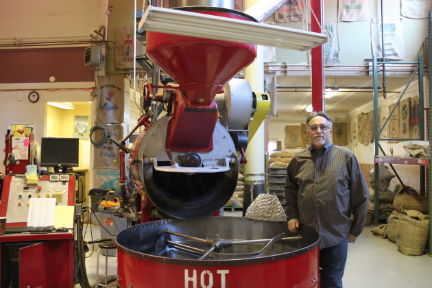 Heritage Coffee Roasting Co. founder Grady Saunders stands in front of the company's roaster, which once belonged to Starbucks Coffee Co. (Photo by Lisa Phu/KTOO)