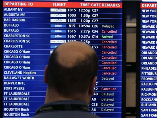 A man looks at a flight departure board filled with weather-related cancellations and delays at Boston's Logan Airport in January. Charles Krupa/AP